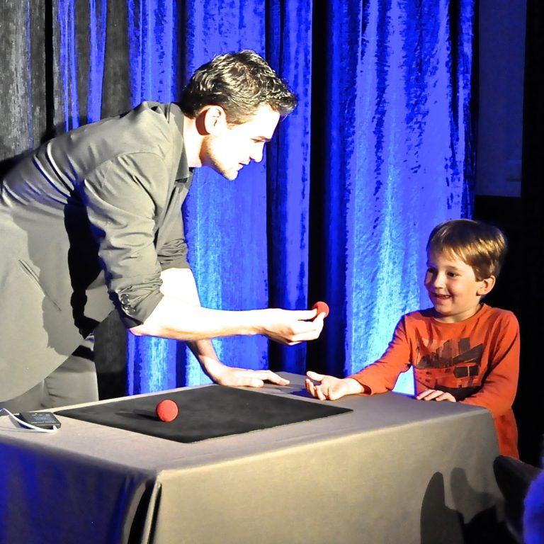 Magicien de Toulon dans un numéro de balle, avec un enfant