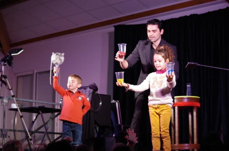 Jérémie Josi, magicien lors d'un anniversaire, présentant un numéros sur le thème des perles, avec la participation de deux enfants.