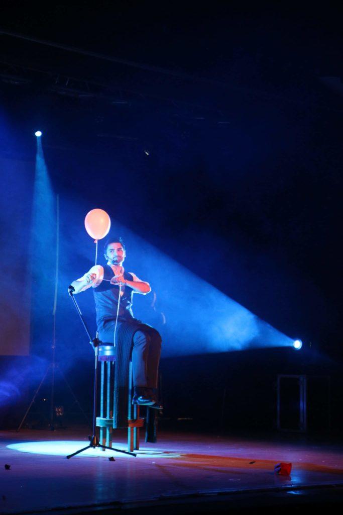 Un magicien lors d'une soirée de gala avec un ballon dans la main qui le fait léviter