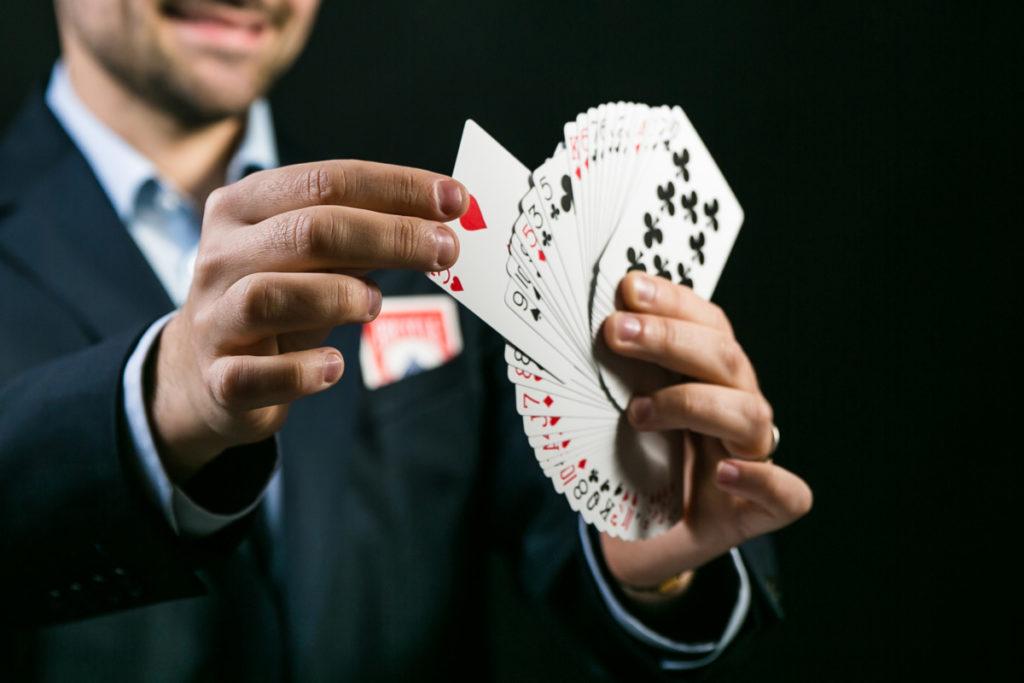 Un magicien tenant un jeu de carte en éventail dans sa main.