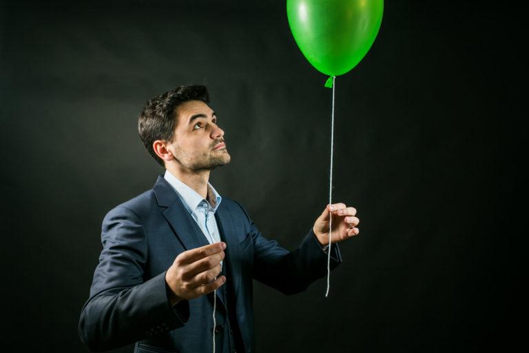 Un magicien qui tient dans sa main un ballon vert avec une ficelle. Celle ci est cassé en deux, un peu de magie et elle sera raccommodée.