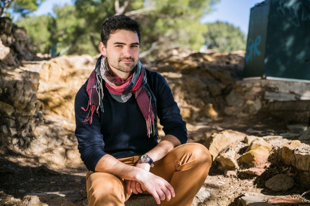 Un magicien assis sur un mur de pierre