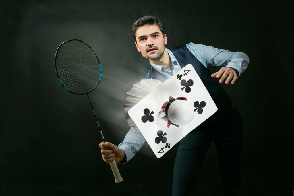 Un magicien avec un numéro sur le thème du badminton, Un volant de badminton attrape une carte dans les airs.