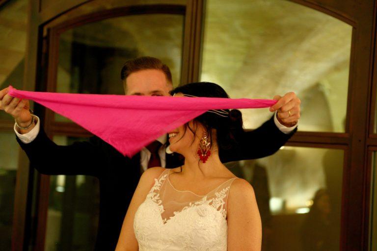 Le marié couvrant les yeux de son épouse par un foulard rose.
