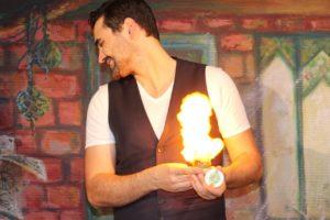 Un magicien avec une explosion de feu dans la main, dans un décor de Jules Verne. Ce spectacle de magie va bientôt faire intervenir un enfant
