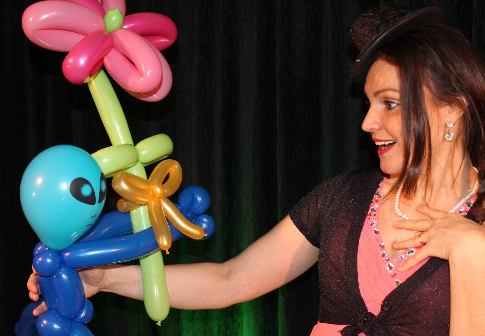 Une magicienne avec dans la main une sculpture sur ballon représentant un extra terrestre qui lui offre un bouquet de fleur.